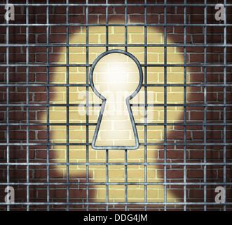 Creative freedom key with a human head light glowing on a brick wall through a prison cage opened with a keyhole - Stock Photo