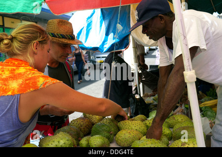 Tourist purchasing Soursop at fruit and vegetable market, St. George's capital of Grenada, Caribbean - Stock Photo