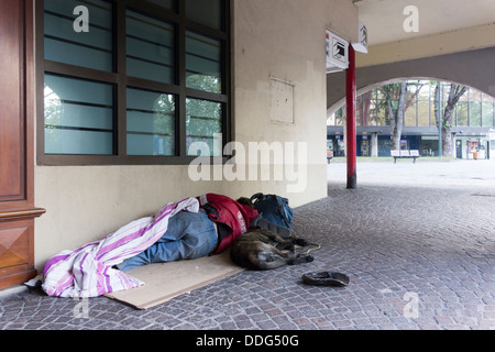 homeless man with dog sleeping on pavement, Annecy, France - Stock Photo