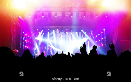 People in the audience with hands up having fun at a music concert / disco party. - Stock Photo