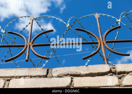 Barbed wire on the fence against a bright blue sky - Stock Photo