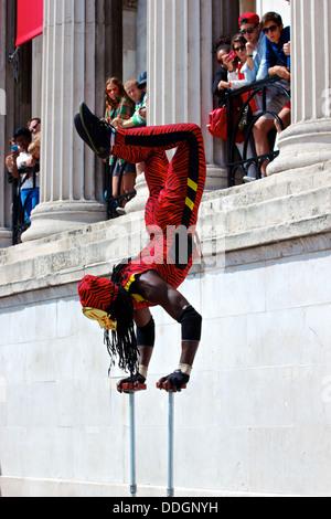 Contortionist street performer Yogi Laser in gold mask balancing on his hands Trafalgar Square London England Europe - Stock Photo