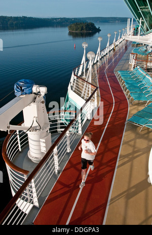 Young woman jogging on a luxury cruise ship at sunrise - Stock Photo