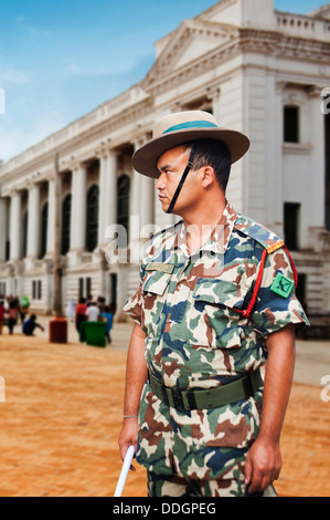 Army soldier standing on the road with a building in the background, Nepal - Stock Photo