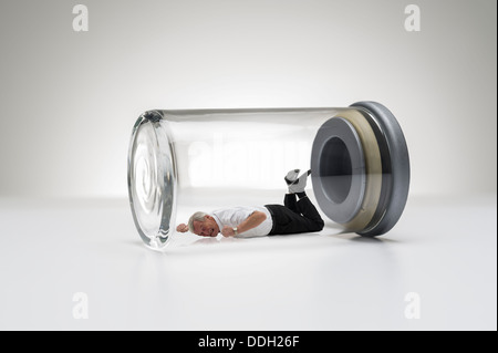 Senior man trapped in a glass jar - Stock Photo
