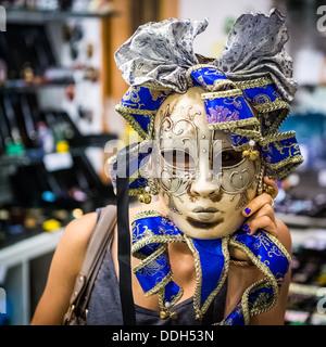 Young woman wearing a venetian carnival mask - Stock Photo