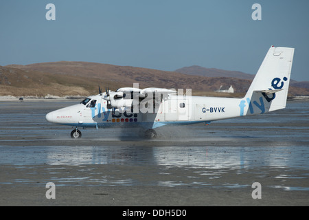 Flybe Twin Otter airplane landing on the Traigh Mhòr beach runway of  Barra Eoligarry Airport, Isle of Barra, - Stock Photo