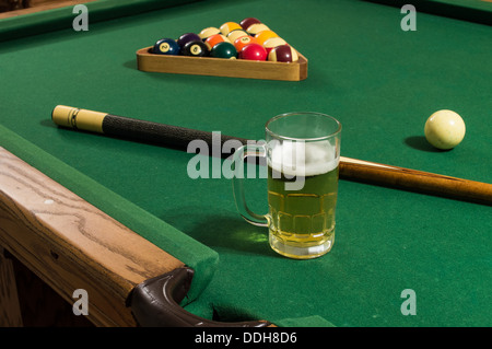 a cold mug of beer with foam on a pool table with green felt, a pool stick and rack of 15 balls including 8 ball - Stock Photo