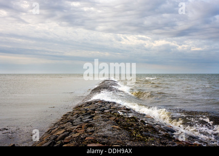 Waves breaking on a pier in the sea - Stock Photo