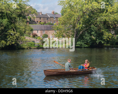 Young couple enjoying a romantic summer afternoon in a boat on a river. - Stock Photo