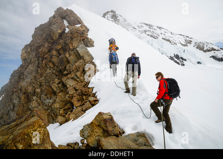 Climbers on the ridge of the Jungfraujoch, near Grindelwald Switzerland, with the south-west ridge of the Monch - Stock Photo