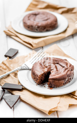 Two chocolate fondants on white rustic wooden table - Stock Photo