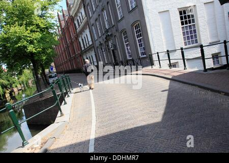 Man walks with his dog on a bridge in the city of Amersfoort, Utrecht province, Netherlands - Stock Photo