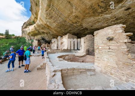 Tourists at Spruce Tree House ruins, ancient Anasazi pueblo dwellings, Mesa Verde National Park, Cortez, USA - Stock Photo