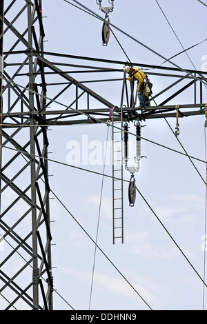 High voltage technician installing a new high-voltage power line - Stock Photo