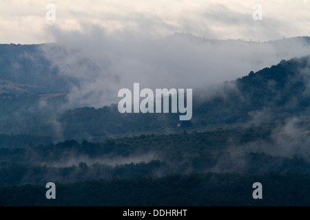 early morning low lying cloud cover rising up through the hills around Piegaro near Perugia in Umbria - Stock Photo