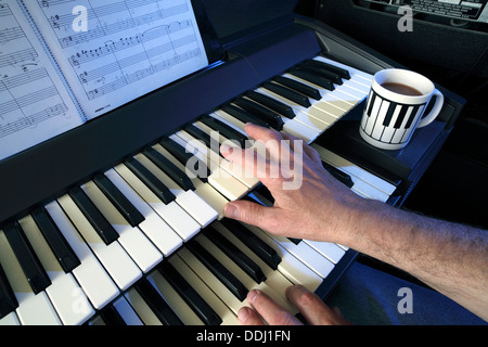 Playing a two manual electric keyboard (and cup of coffee). - Stock Photo