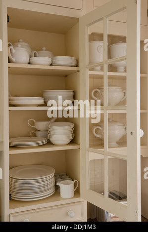 Assorted white china in an open kitchen cupboard - Stock Photo