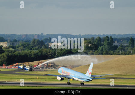 A Thomson Boeing 757 aircraft takes off whilst an airport fire engine sprays water in the background. - Stock Photo