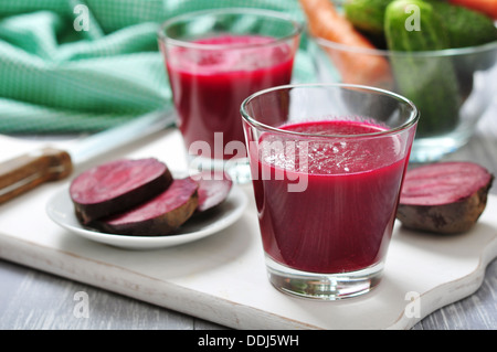 Beetroot juice in glass on wooden cutting board - Stock Photo