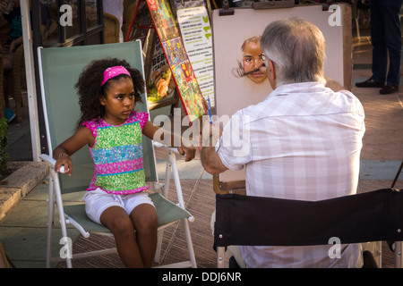 A pavement artist in the Andalusian seaside town of Nerja captures the beauty of a pretty young girl as she sits - Stock Photo