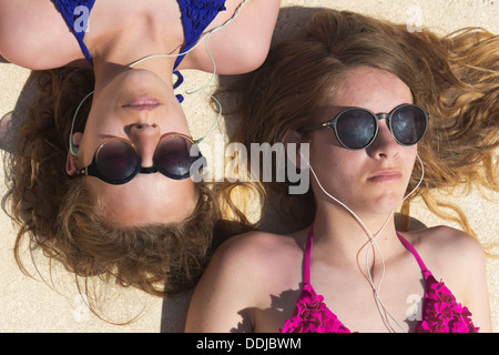 Two teenage girls lying in the sun listening to music on their mobile phones. - Stock Photo