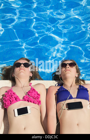 Two teenage girls lying in the sun by the pool listening to music on their mobile phones. - Stock Photo