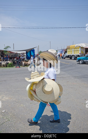 Woman walking along a road in Mexico carrying and wearing  hats ( sombreros ) to sell on market day. - Stock Photo