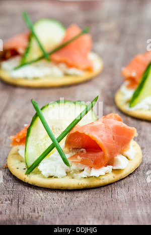 Canapes with smoked salmon, cucumber and cream cheese, selective focus, closeup - Stock Photo