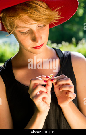 Young woman, wearing a red felt hat and a black dress, gently pulling the petals from a daisy - Stock Photo