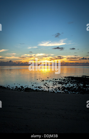 Sunset colors with reflection over the ocean at Amuri Beach in Aitutaki Island, Cook Islands - South Pacific Ocean - Stock Photo