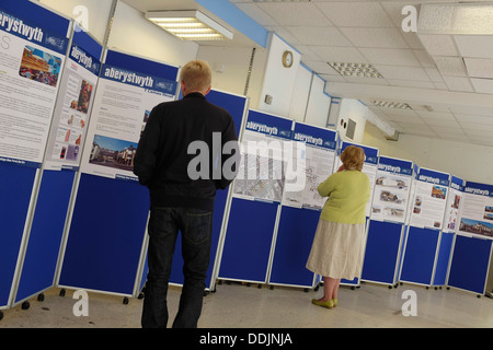 Two People looking at information panels during the public consultation on proposed Tesco / Marks & Spencer development - Stock Photo