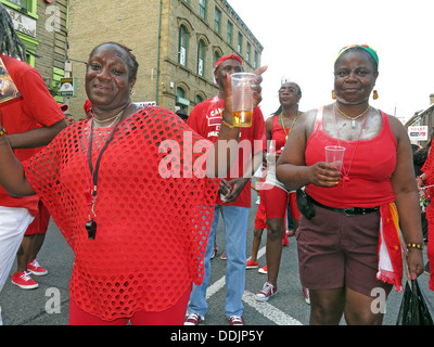 Costumed dancers in red from Huddersfield Carnival 2013 African Caribbean parade street party - Stock Photo