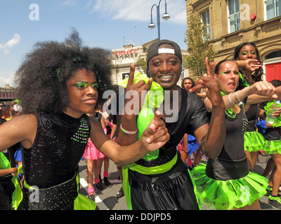 Costumed dancers in green from Huddersfield Carnival 2013 African Caribbean parade street party - Stock Photo