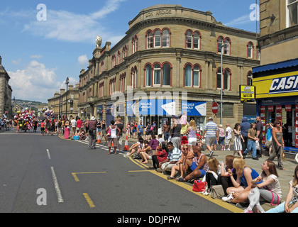 Crowds await costumed dancers from Huddersfield Carnival 2013 African Caribbean parade street party - Stock Photo