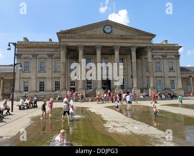 Square outside Huddersfield railway station with fountains and sculpture of Harold Wilson by Ian Walters - Stock Photo