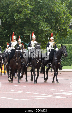 Changing the Guards at Buckingham Palace walking up the Mall - Stock Photo