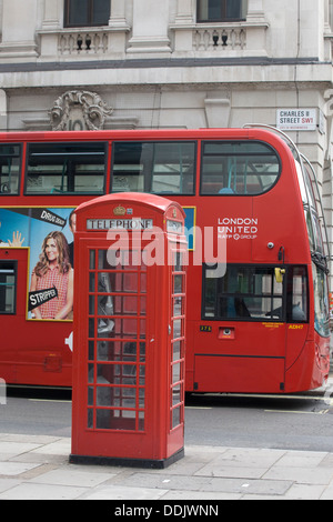 Double decker bus advertising Meet the Millers with a Red Telephone Box on the streets of London England - Stock Photo