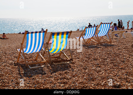 Deckchairs on Brighton beach, East Sussex, England, UK - Stock Photo