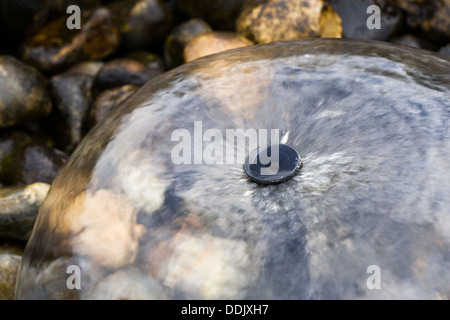 Small water fountain in an English garden. - Stock Photo