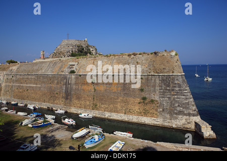 The high and steep defense walls of the Old Fortress in Corfu Town in Greece which is built on a rocky peninsula. - Stock Photo