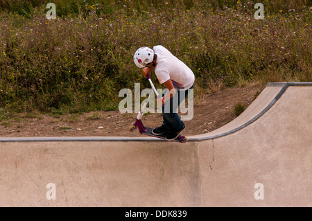 Young Boy performing stunts on a scooter - Stock Photo