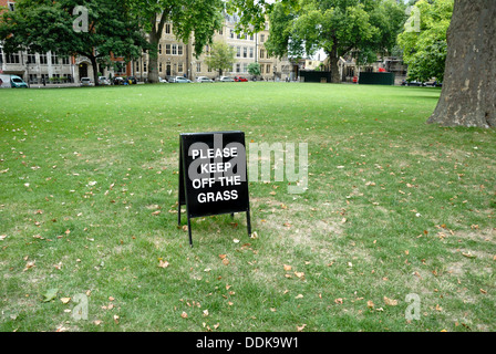 London, England, UK. 'Please Keep off the Grass' sign in Dean's Yard, behind Westminster Abbey - Stock Photo