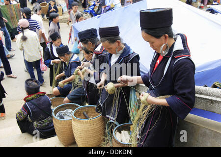 Women in traditional costume spinning hemp at market, Sa Pa. Lao Cai, Vietnam - Stock Photo