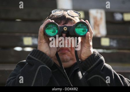 A racegoer watches a horse race during the 122nd Velka Pardubicka Steeplechase in Pardubice, East Bohemia, Czech - Stock Photo