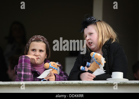 Young racegoers look on horse races during the 122nd Velka Pardubicka Steeplechase in Pardubice, East Bohemia, Czech - Stock Photo