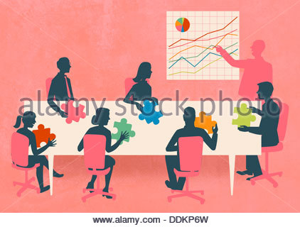 Business people with multicolored jigsaw puzzle pieces in meeting - Stock Photo