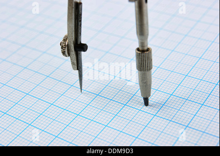 Drawing compass on graph paper - Stock Photo