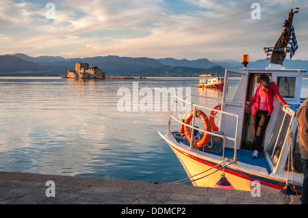 A ferry boat in the harbour at Nafplio with the Bourtzi island and fort in the background, Argolid, Peloponnese, - Stock Photo