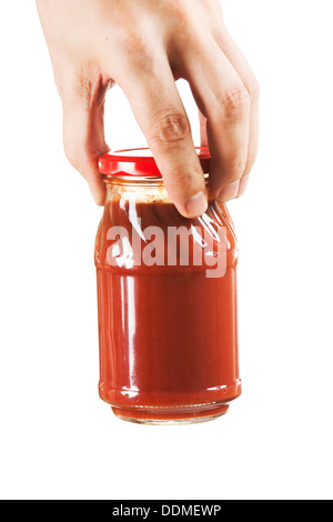 jar tomato paste in hand isolated on white background - Stock Photo